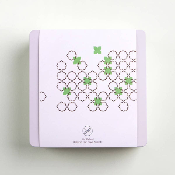The top view of a 2021 Hari Raya cookie gift box sleeved in white with Arabic Islamic patterns and pops of green