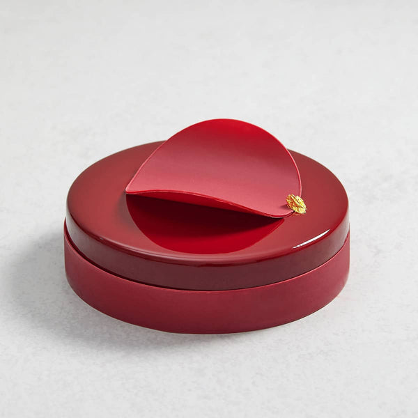 A closeup of a Raspberry Valrhona Jivara Mousse cake with a Raspberry chocolate decoration and edible gold leaf