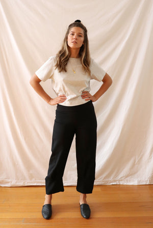ethically made black stretch pants with pockets and three-quarter cuff.