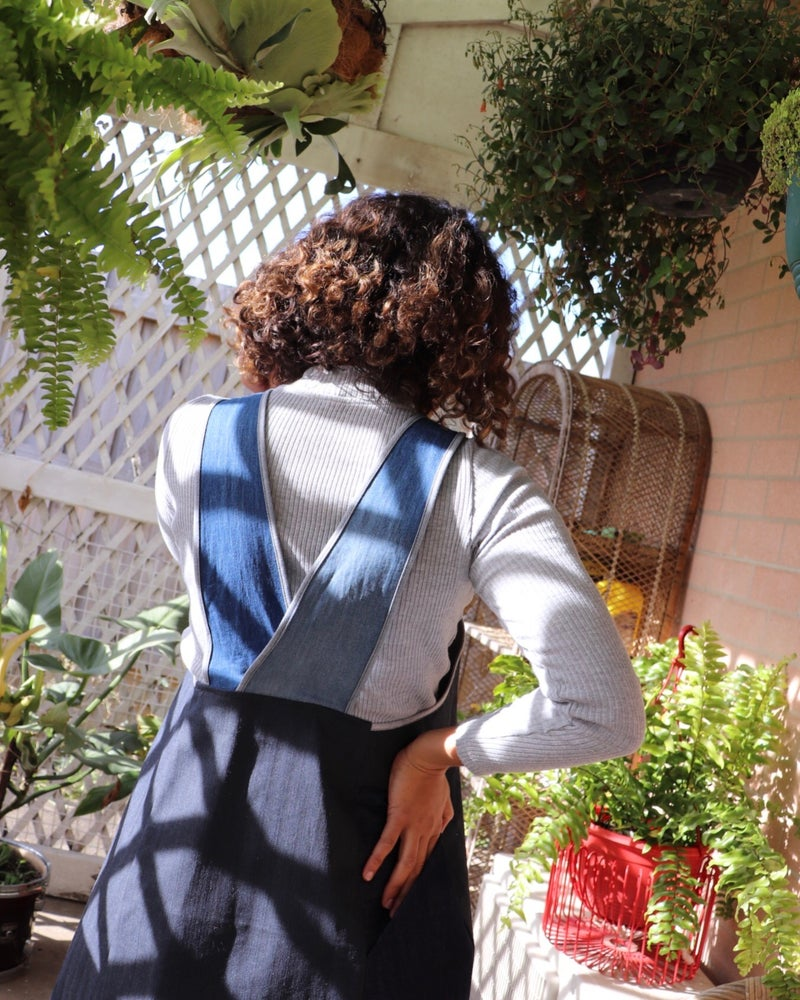 Ethically made pinafore style dress in blue denim cotton with one pocket. Mid length and short.