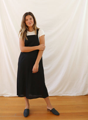 Ethically made pinafore style dress in black linen with one pocket. Mid length and short.