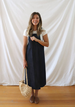 Ethically made pinafore style dress in blue denim with one pocket. Mid length and short.