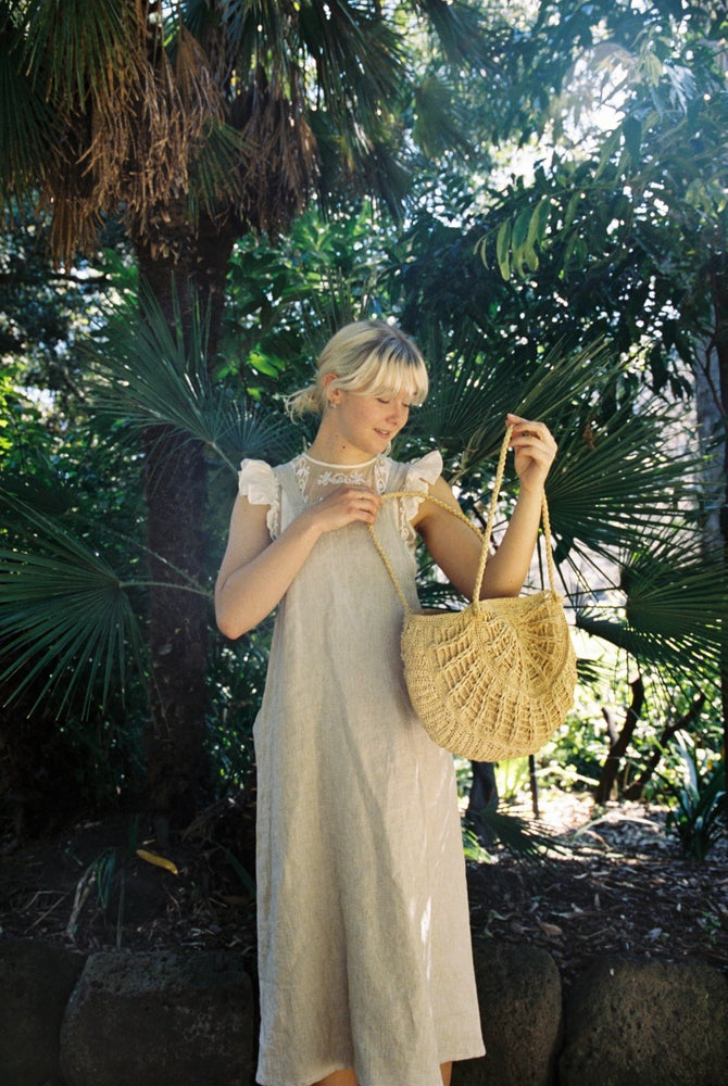Ethically made pinafore style dress in oatmeal beige linen cotton with one pocket. Mid length and short.