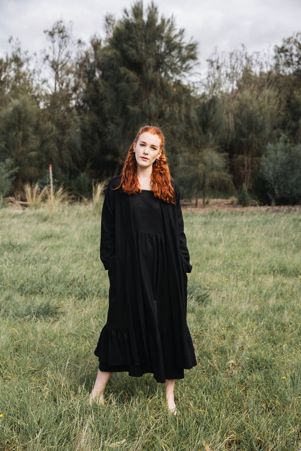 Ethically made long coat with side pockets and waist-tie in black cotton linen mix.