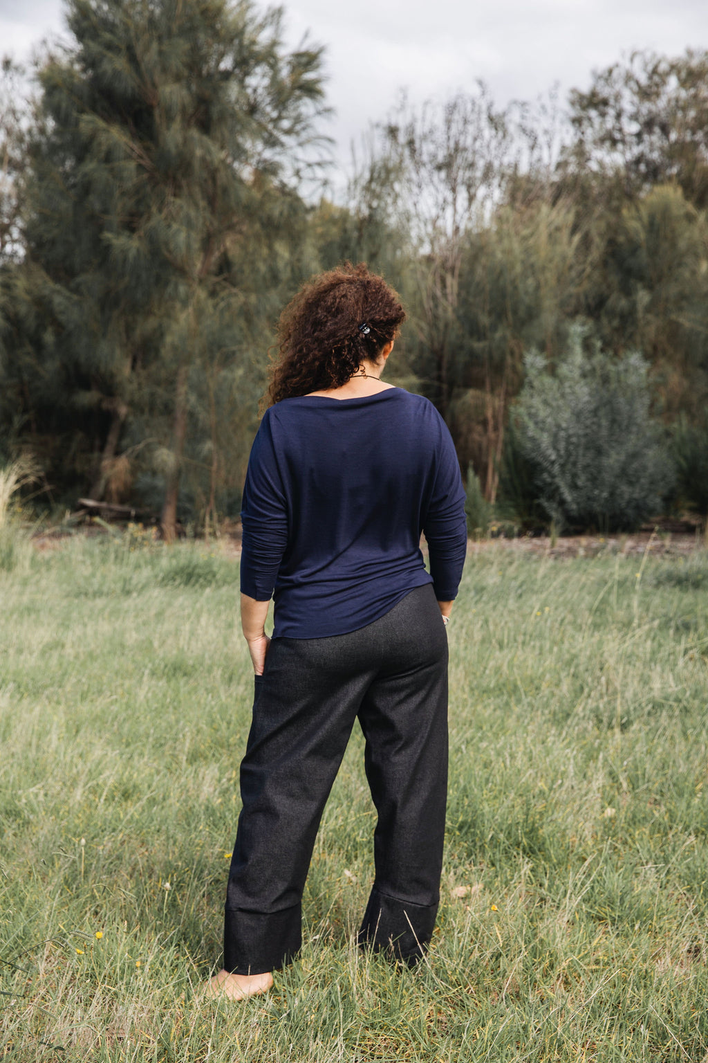 Ethically made black denim stretch pants with pockets and three-quarter cuff.