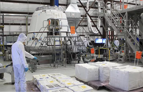 Bright orange FOD bags dispersed around a SpaceX Dragon cleanroom or hangar.  Photo courtesy of SpaceX.