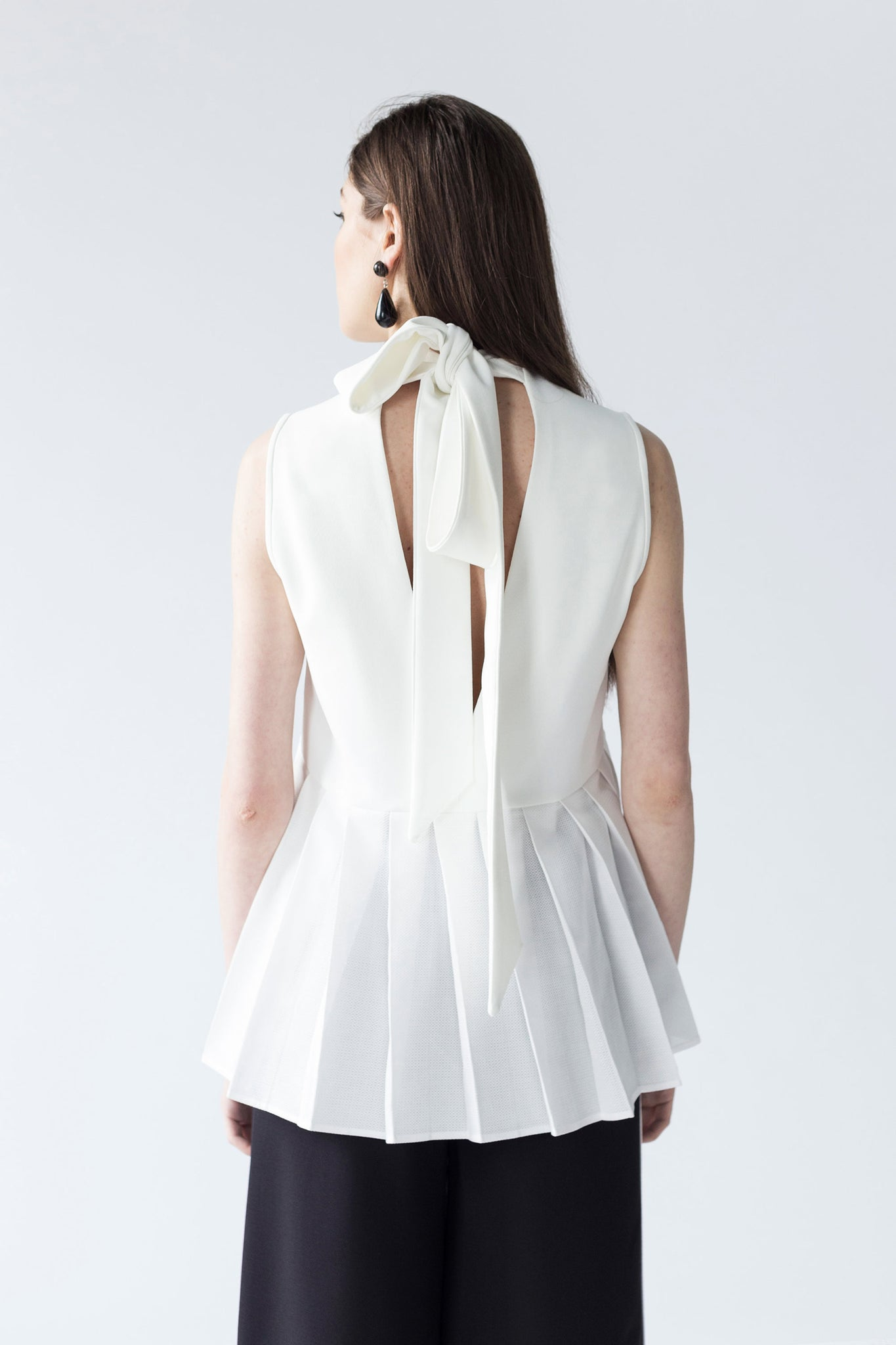 PLEATED-PANELLED TOP WITH GROWING NECKLINE AND BACK BOW