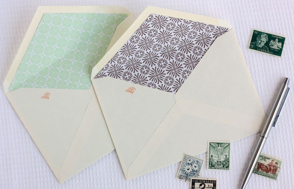 Lined envelopes next to stamps and pen
