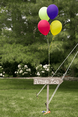 Sign with balloons attached reading Petting Zoo at barn wedding