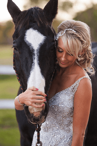 Woman in wedding dress posing next to brown horse_photo by Blue Tulip Imaging