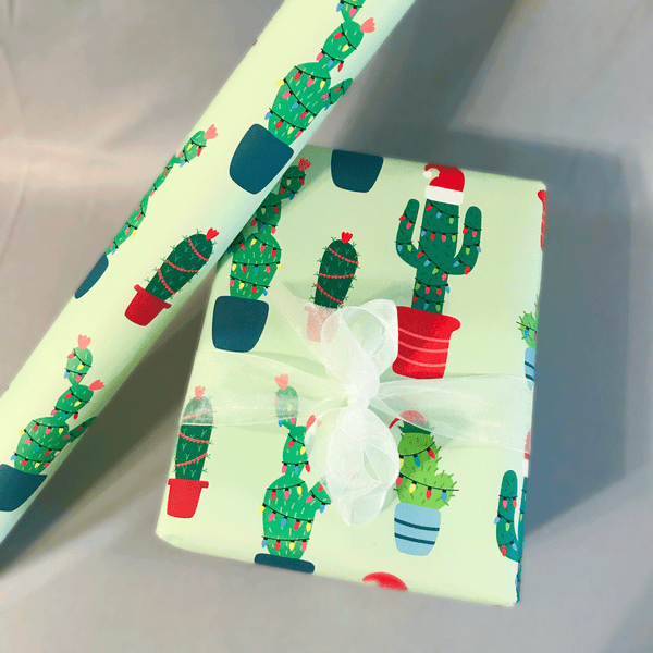 Christmas Cactus Gift Wrap - Illustrated Holiday Wrapping Paper with 4 Unique Cactus Plants Decorated in Christmas Lights - Gift Wrapped Box with Ribbon next to Roll