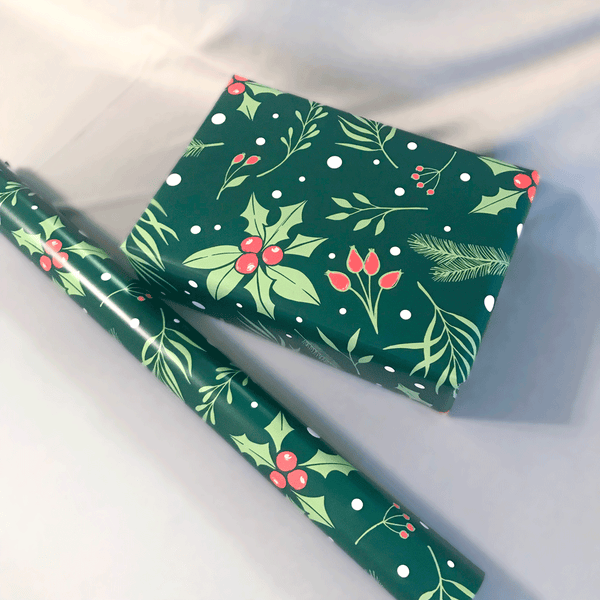 Green Holly Berry Print Holiday Gift Wrap - Designer Wrapping Paper Sheets - Wrapped Gift Box next to Wrapping Paper Roll