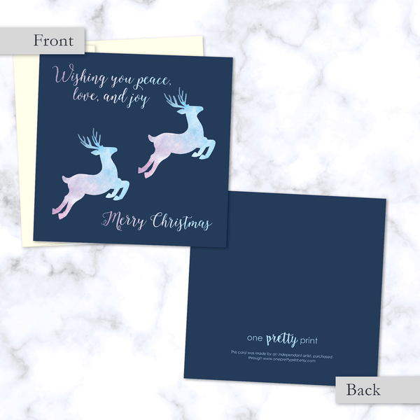 Leaping Reindeer Square Folded Christmas Card. Front and Back View. With Watercolor Textured Reindeer in Pink and Blue - Envelope Included