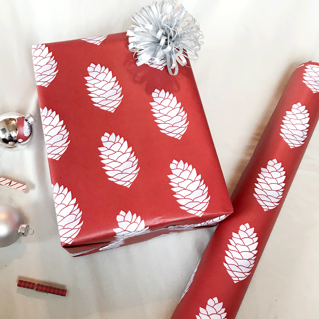 Red Pine Cone Holiday Gift Wrap - Designer Wrapping Paper Sheets - Wrapped Gift next to Gift Wrap Roll and Christmas Ornaments