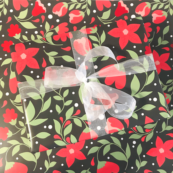 Red Poinsettia Floral Print Holiday Gift Wrap - Designer Wrapping Paper Sheets - Wrapped Gift Box with Ribbon on top of flat wrapping paper sheet