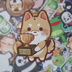 Air freshener featuring a shiba holding a trophy