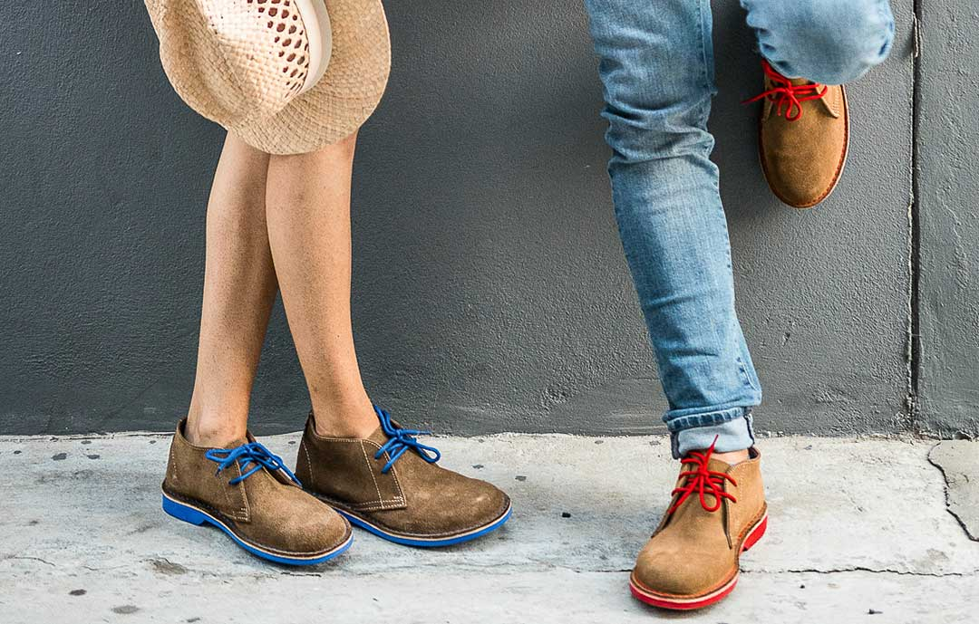 Women and man standing back against the wall only see the bootm half wearing blue sole and red sole chukka boots suede from veldskoen