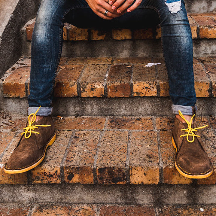 Veldskoen shoes and boots or known as vellies heritage boot ethically and sustainably handcrafted in South Africa sold in united states man sitting on a brick staircase wearing yellow Veldskoene and blue jeans