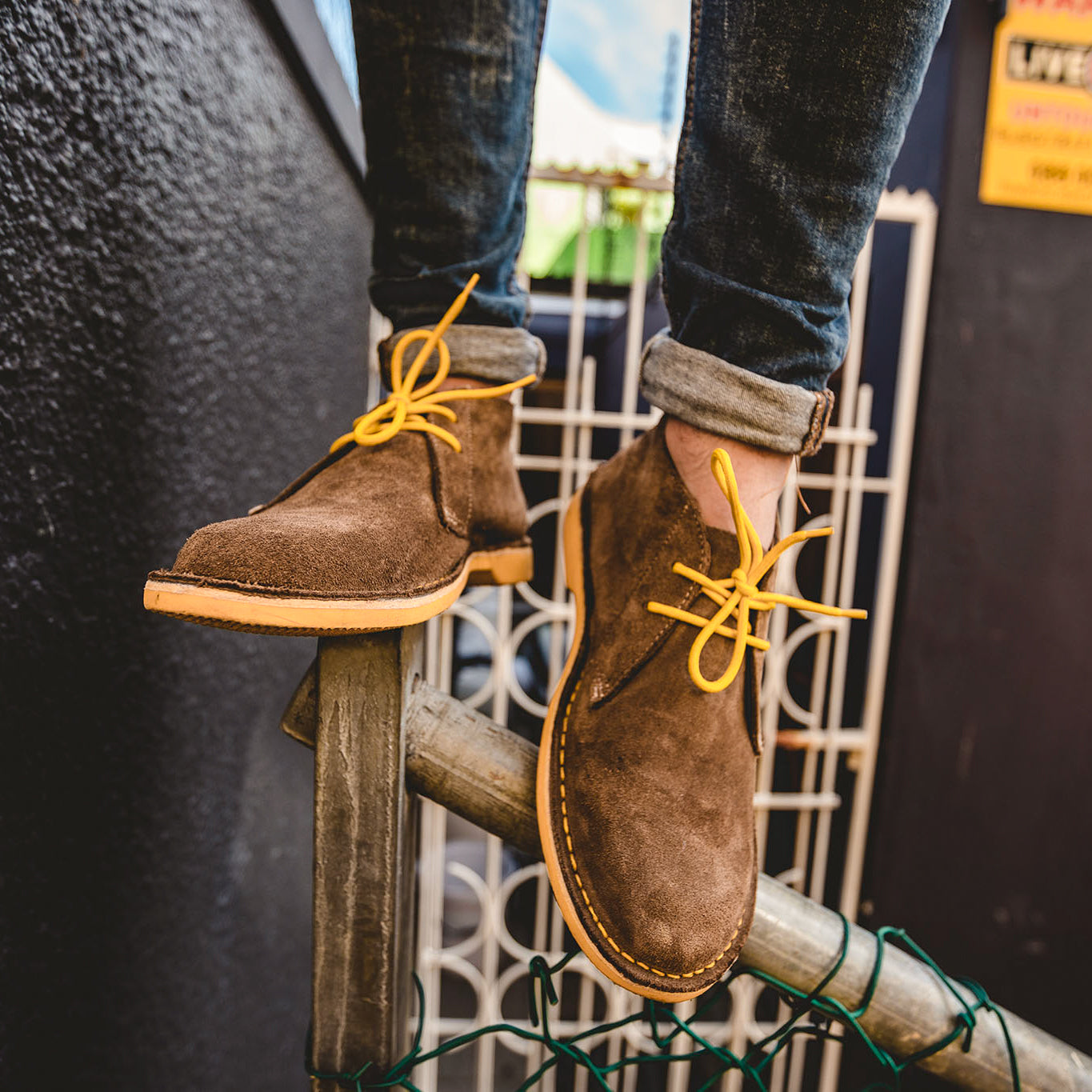 Veldskoen shoes and boots or known as vellies heritage boot ethically and sustainably handcrafted in South Africa sold in united states man standing on fence wearing jeans and yeallow Veldskoene