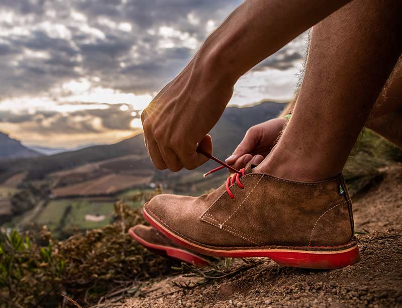 Man wearing red soled Veldskoen shoes ethically handcrafted genuine leather boots and shoes from South Africa in the bush mountain region