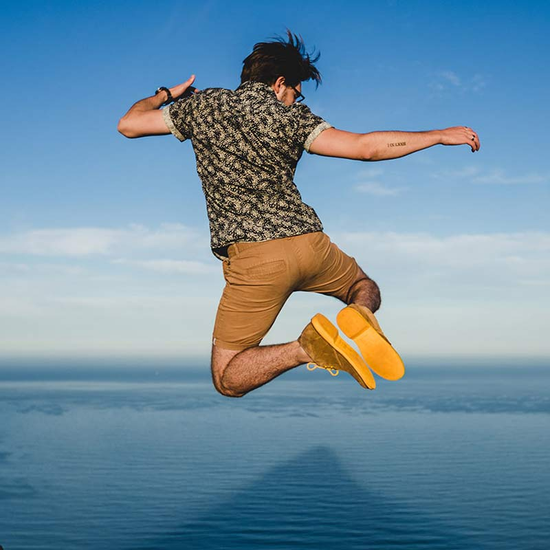 Veldskoen shoes and boots or known as vellies heritage boot ethically and sustainably handcrafted in South Africa sold in united states man jumping infrom of water wearing short and Yellow veldskoene