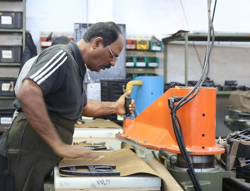 Man working on ornage machine cutting leatherVeldskoen shoes ethically handcrafted genuine leather boots and shoes from South Africa