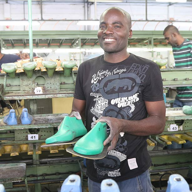 Man at veldskoene factory holding veldskoen shoes Veldskoen shoes ethically handcrafted genuine leather boots and shoes from South Africa