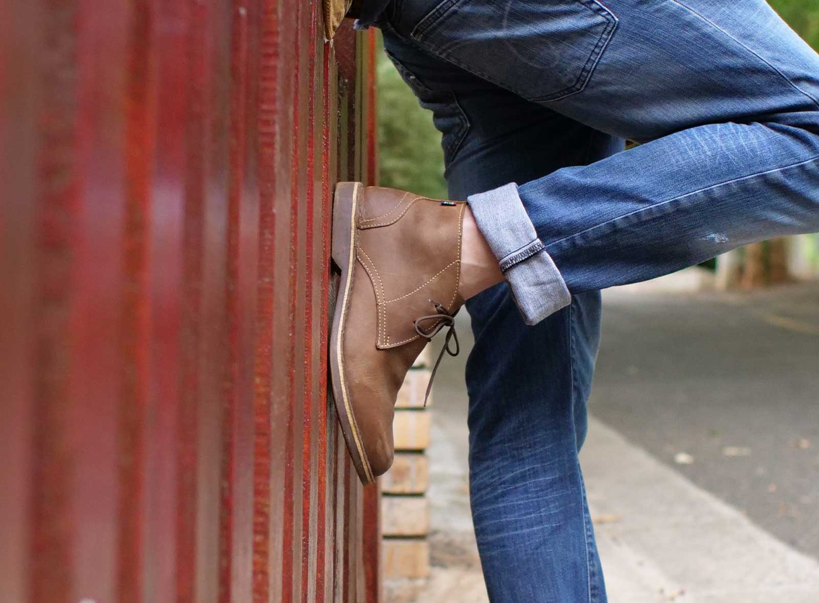 Chukka original shoe Veldskoen shoes ethically handcrafted genuine leather boots and shoes from South Africa man in jeans standing against wall
