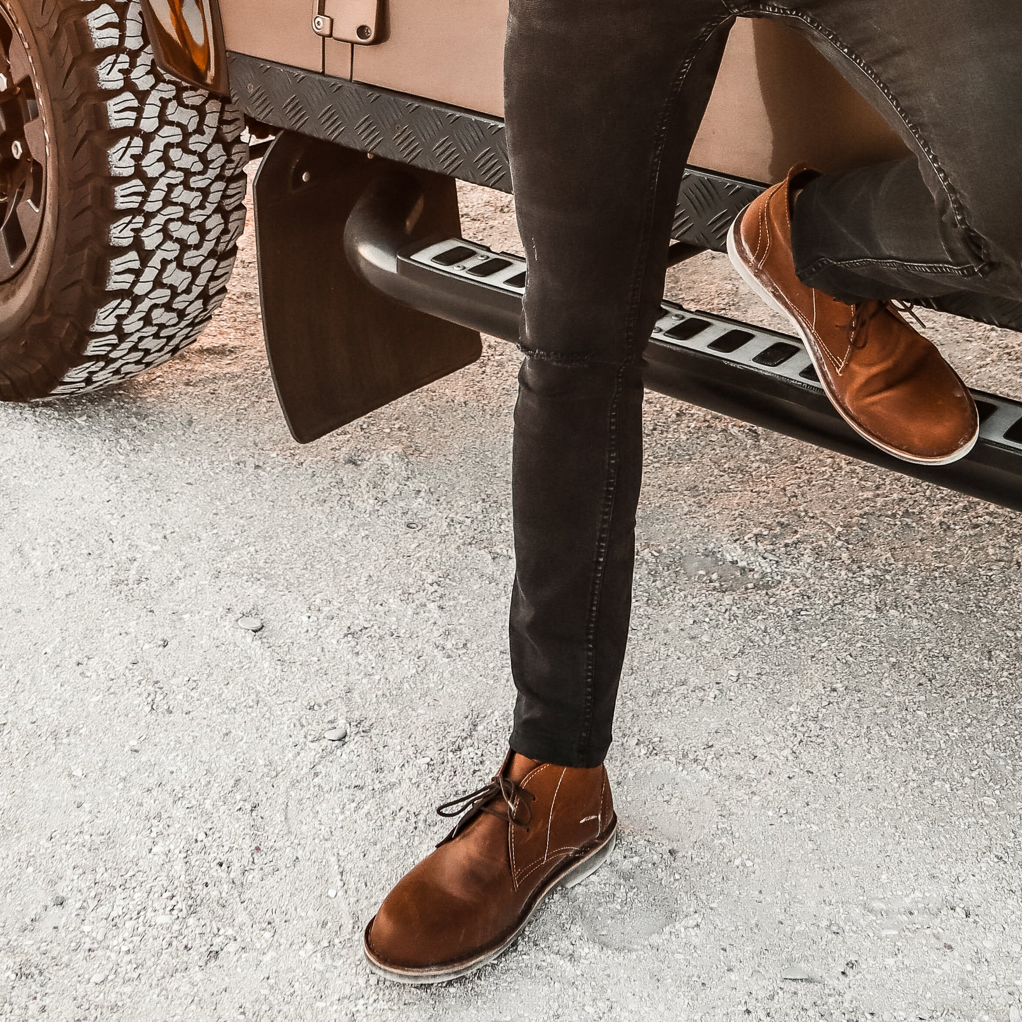 Veldskoen shoes and boots or known as vellies chukka boot ethically and sustainably handcrafted in South Africa sold in united states man standing next to landrover discovery in white sand and wearing black jeans