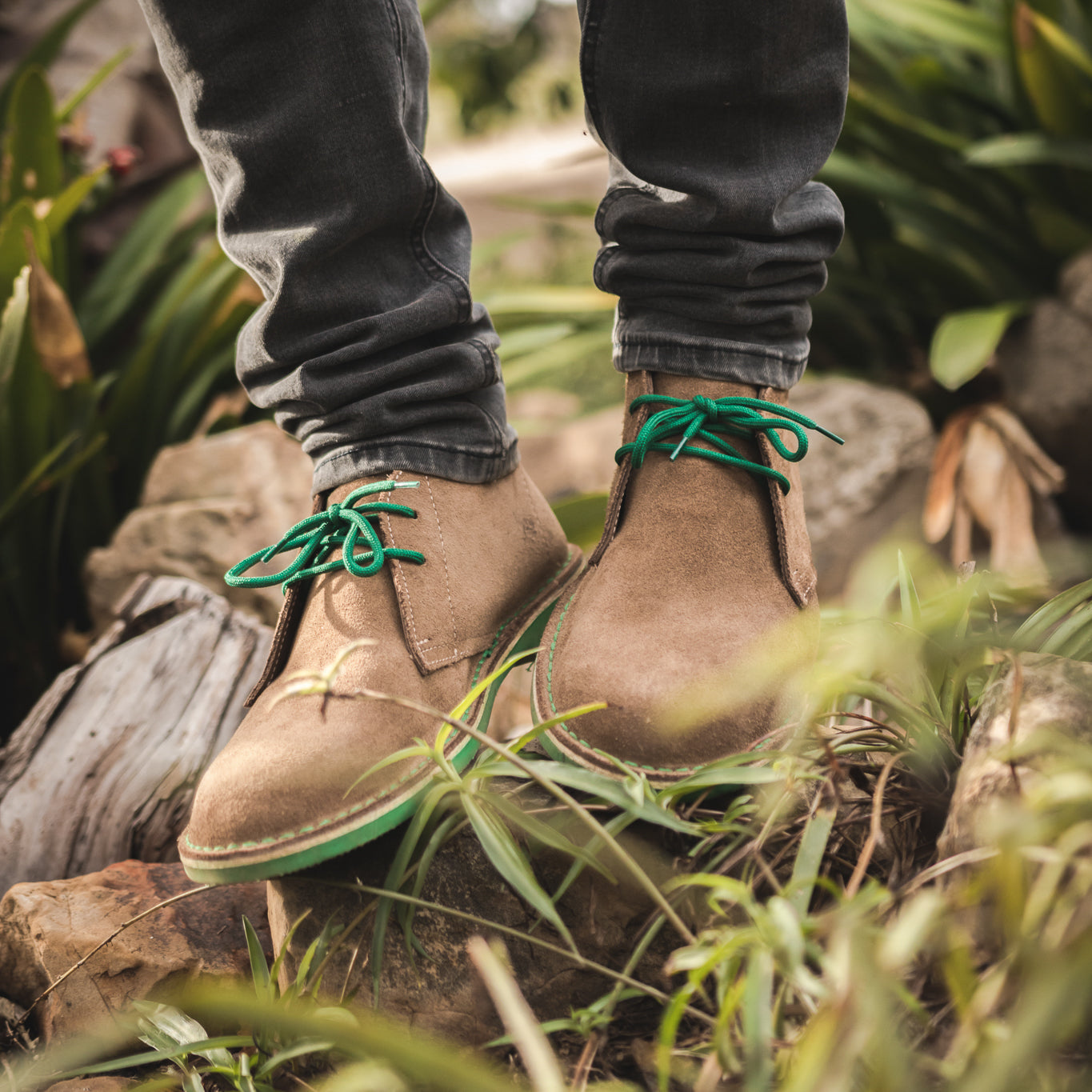 Veldskoen shoes and boots or known as vellies heritage boot ethically and sustainably handcrafted in South Africa sold in united states man wearing green veldskoen and black jeans standing in a garden