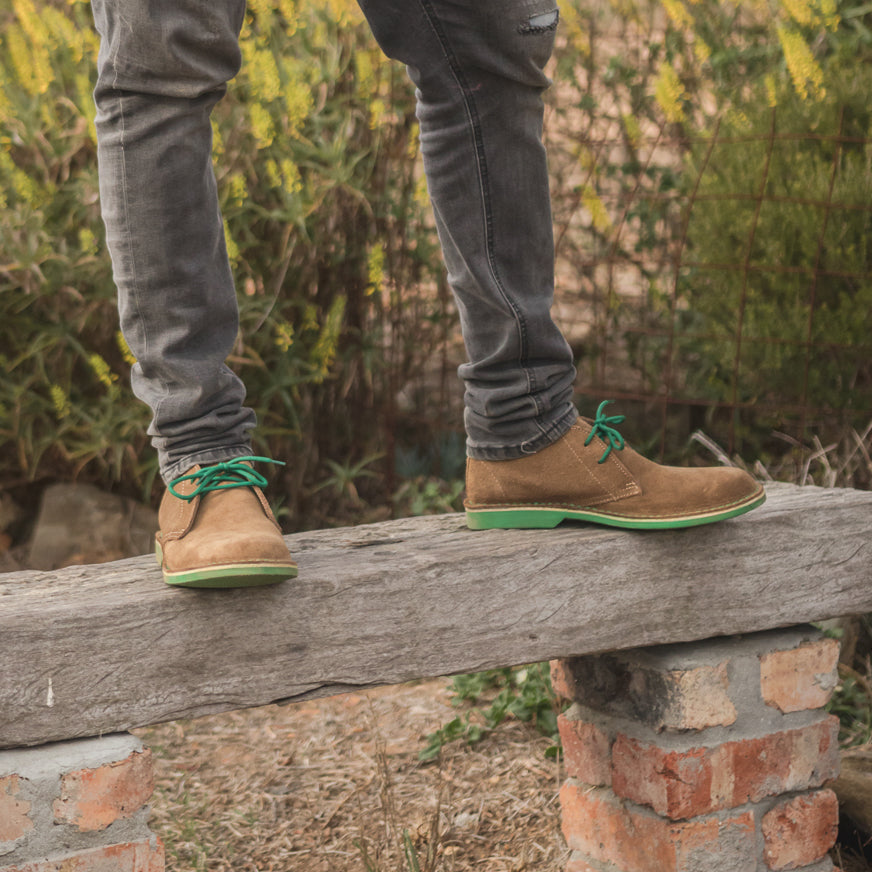 Veldskoen shoes and boots or known as vellies heritage boot ethically and sustainably handcrafted in South Africa sold in united states man standing on wooden platform wearing green Veldskoene and black jeans