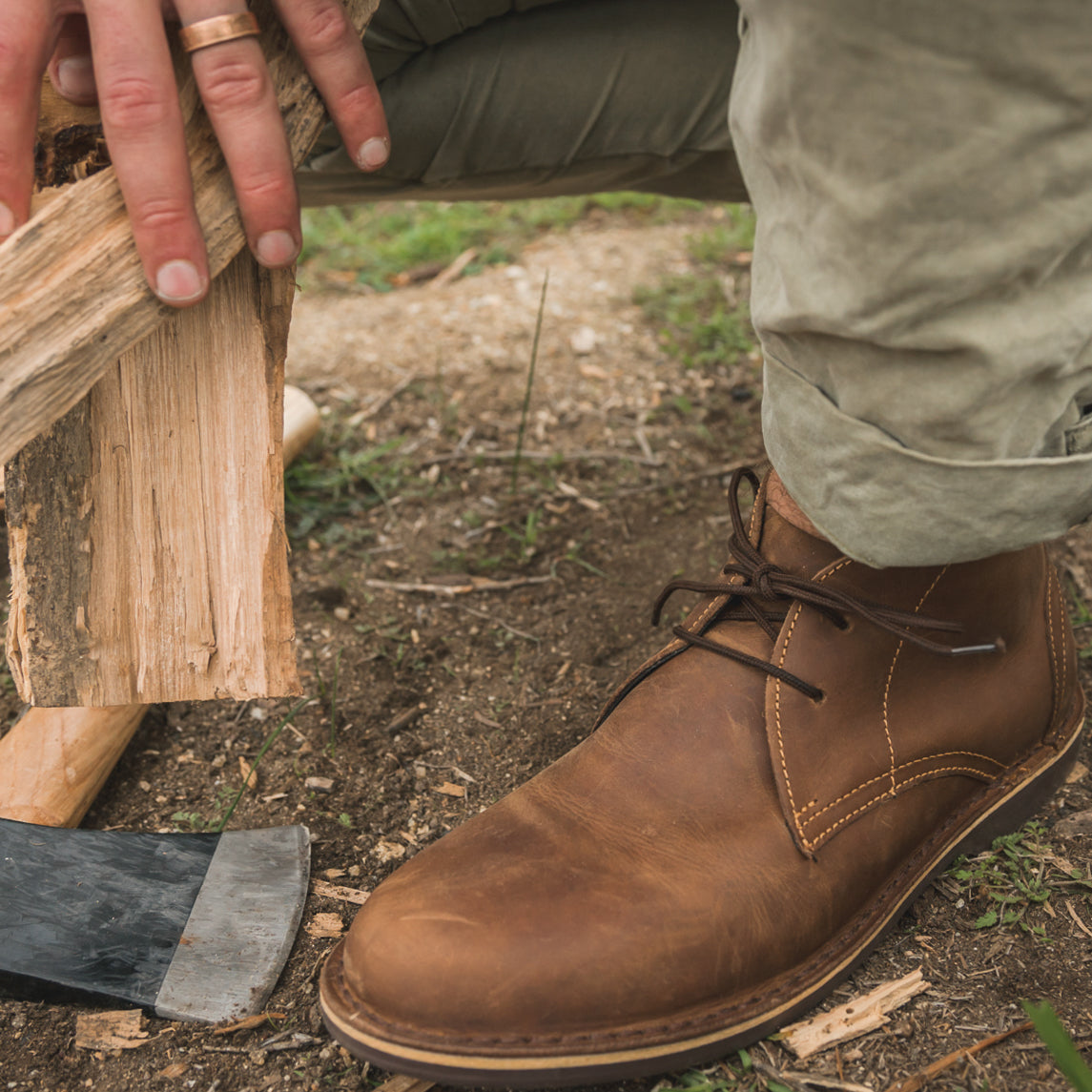 Veldskoen shoes and boots or known as vellies chukka boot ethically and sustainably handcrafted in South Africa sold in united states man holding wood in hands and kneeling in front of a fire with an axe to the side of him