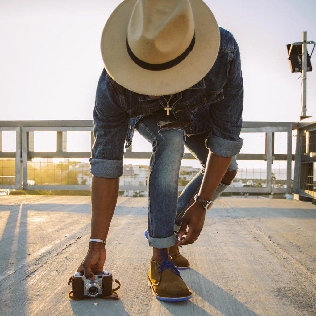 Veldskoen shoes and boots or known as vellies heritage boot ethically and sustainably handcrafted in South Africa sold in united states man wearing jean jacket and rolled up jeans and broad rimmed hat holding camera with blue jbay veldskoen