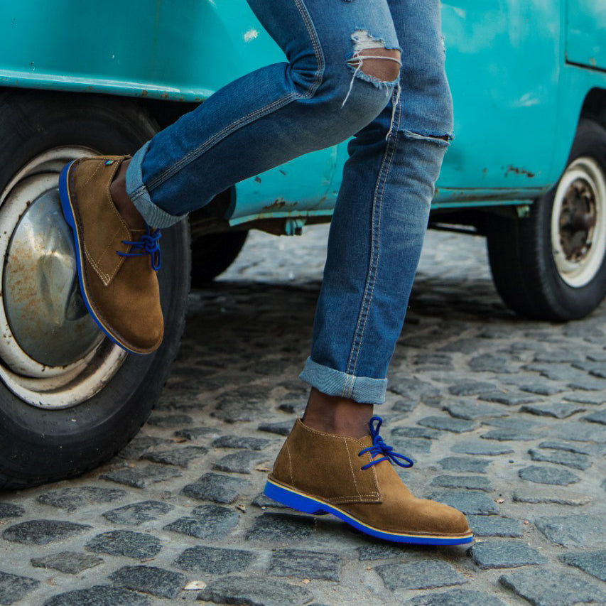 Veldskoen shoes and boots or known as vellies heritage boot ethically and sustainably handcrafted in South Africa sold in united states man wearing blue jeans and blue Veldskoen standing next to VW van