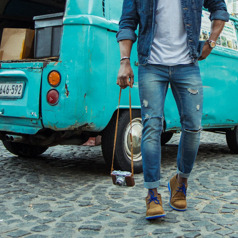Veldskoen shoes and boots or known as vellies heritage boot ethically and sustainably handcrafted in South Africa sold in united states man standing in front of VW van wearing blue veldskoen and blue jeans holding a camera