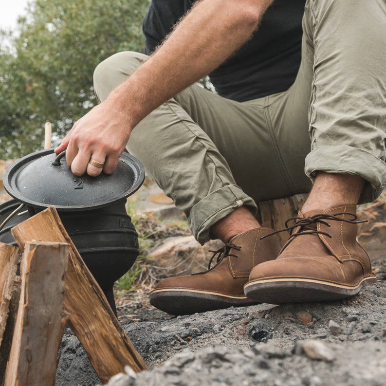 Veldskoen shoes and boots or known as vellies chukka boot ethically and sustainably handcrafted in South Africa sold in united states man using fire pot and knelling on the ground in front of a fire