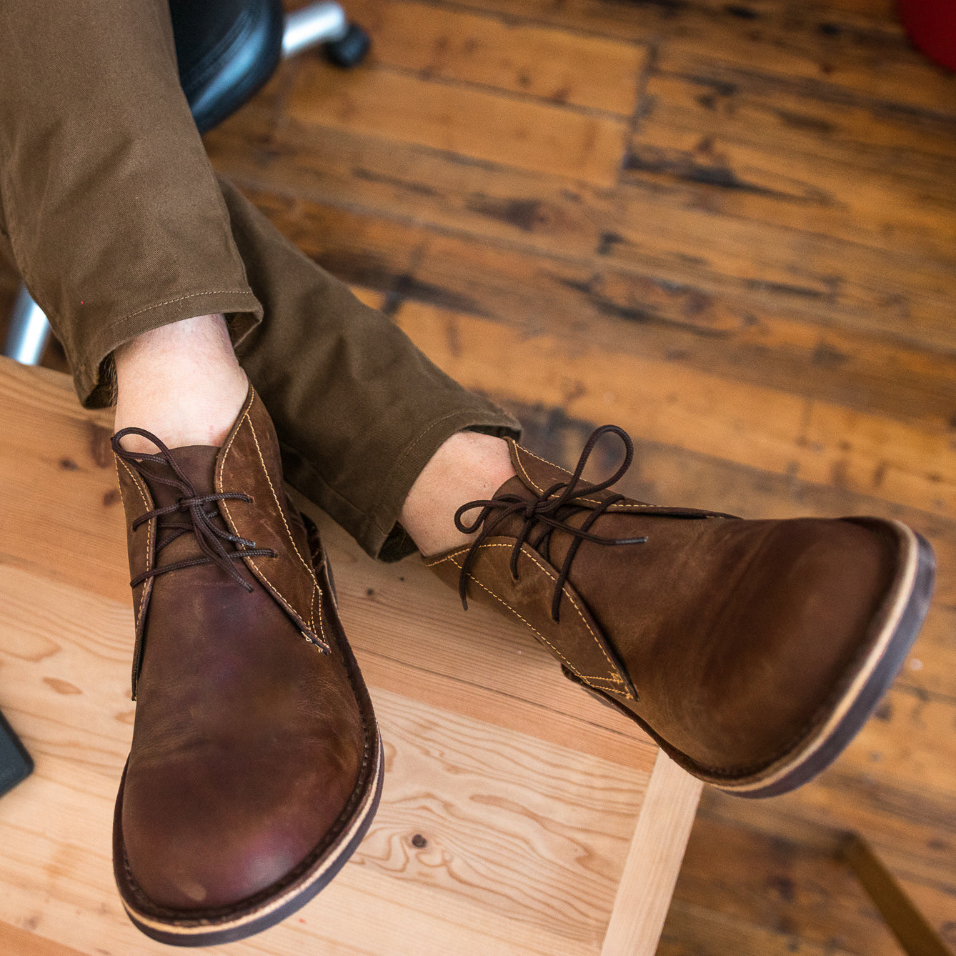 Veldskoen shoes and boots or known as vellies chukka boot ethically and sustainably handcrafted in South Africa sold in united states man sitting with brown pants with feet up on desk in office environment