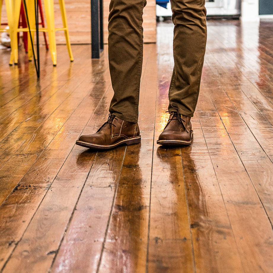 Veldskoen shoes and boots or known as vellies chukka boot ethically and sustainably handcrafted in South Africa sold in united states man standing in office enviroment with long brown pants on wooden floor