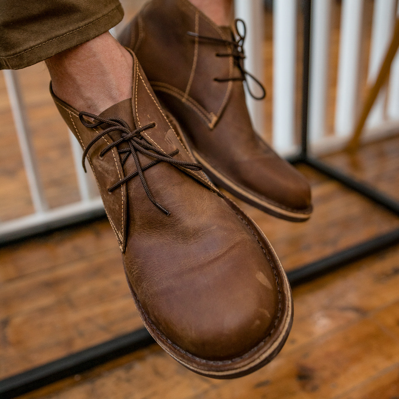 Veldskoen shoes and boots or known as vellies chukka boot ethically and sustainably handcrafted in South Africa sold in united states  man sitting hanging brown leather shoes in chukka style