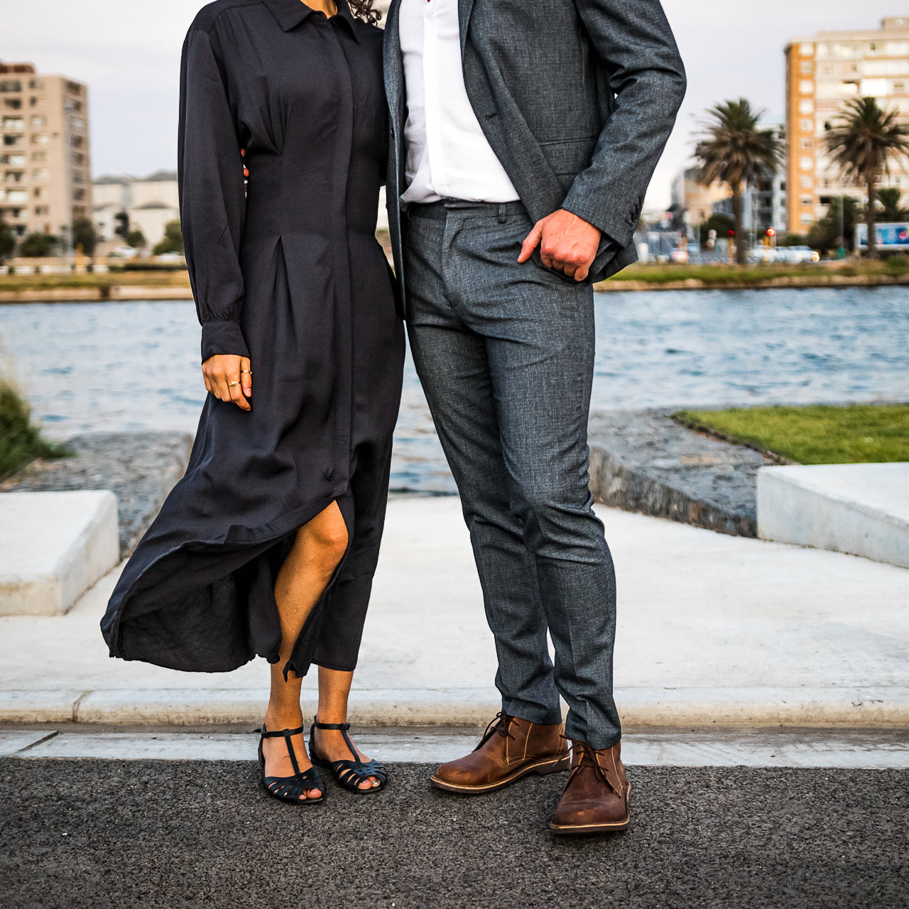 Veldskoen shoes and boots or known as vellies chukka boot ethically and sustainably handcrafted in South Africa sold in united states man and women standing infront on water dressign in smart night wear man wears grey suit and women wears long black dress
