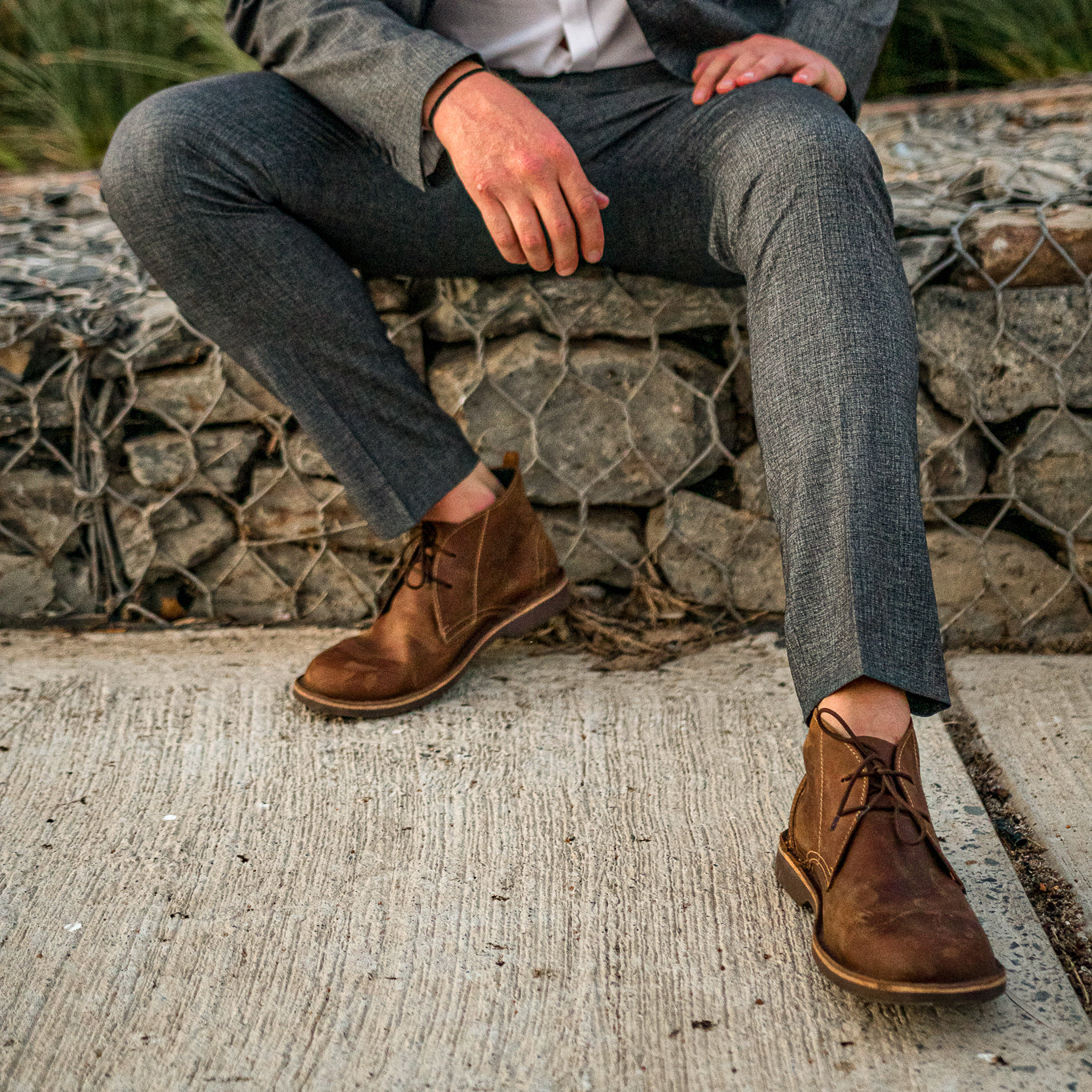Veldskoen shoes and boots or known as vellies chukka boot ethically and sustainably handcrafted in South Africa sold in united states man sitting on brick / stone wall hand on knees with  grey suit and dark brown chukka shoes