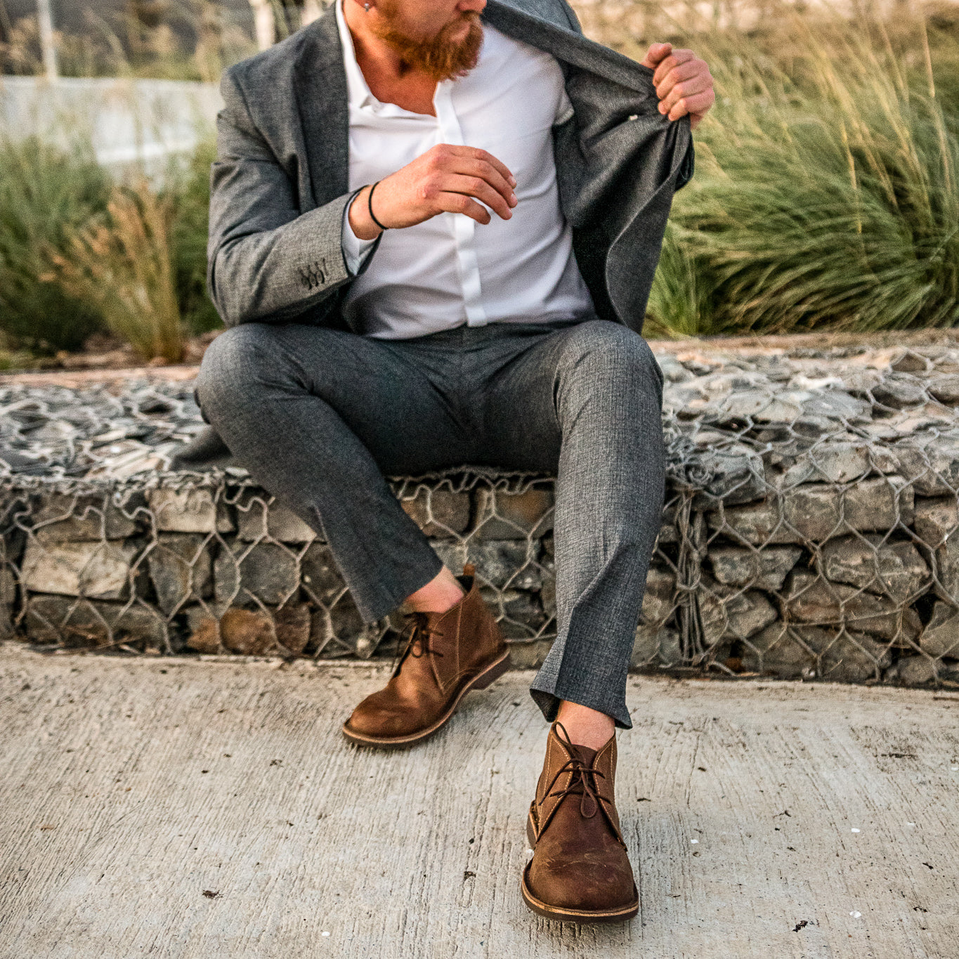 Veldskoen shoes and boots or known as vellies chukka boot ethically and sustainably handcrafted in South Africa sold in united states man sitting looking inside his grey jacket sitting on wall wearing dark brown chukka boots
