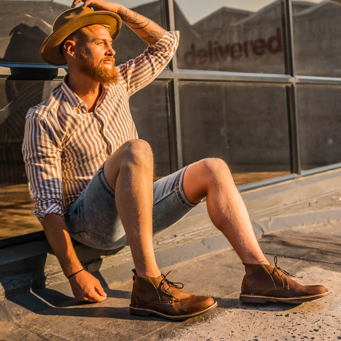 Veldskoen shoes and boots or known as vellies chukka boot ethically and sustainably handcrafted in South Africa sold in united states  man with denim cut off shorts and wearing fidora hat and dark brown veldskoen chukka boots