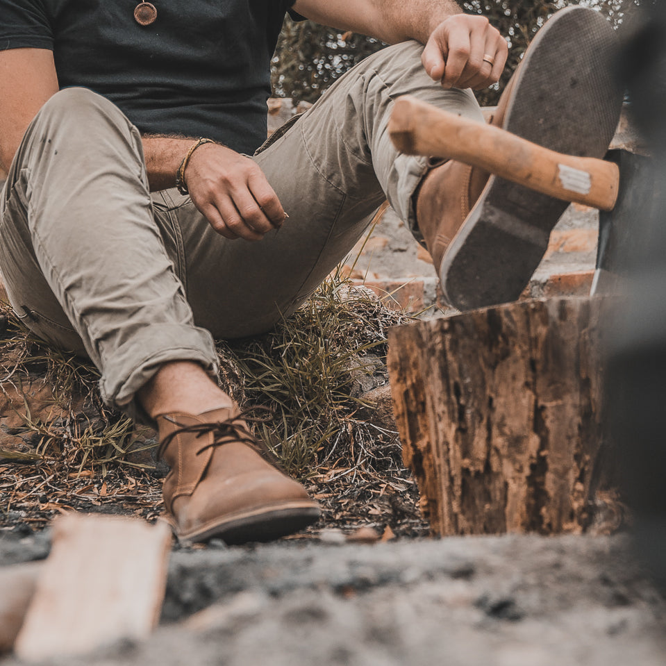 Veldskoen shoes and boots or known as vellies chukka boot ethically and sustainably handcrafted in South Africa sold in united states man in the bush wearing green pant and foot up on an axe