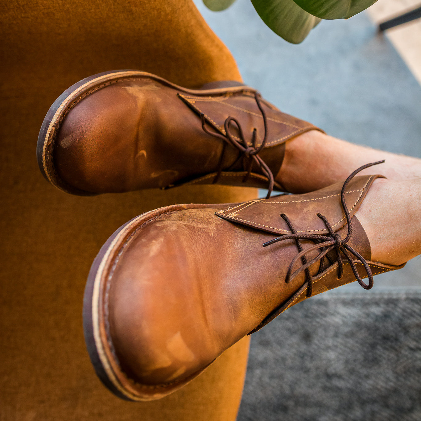 Veldskoen shoes and boots or known as vellies chukka boot ethically and sustainably handcrafted in South Africa sold in united states closeup of man with chukka boot resting on chair