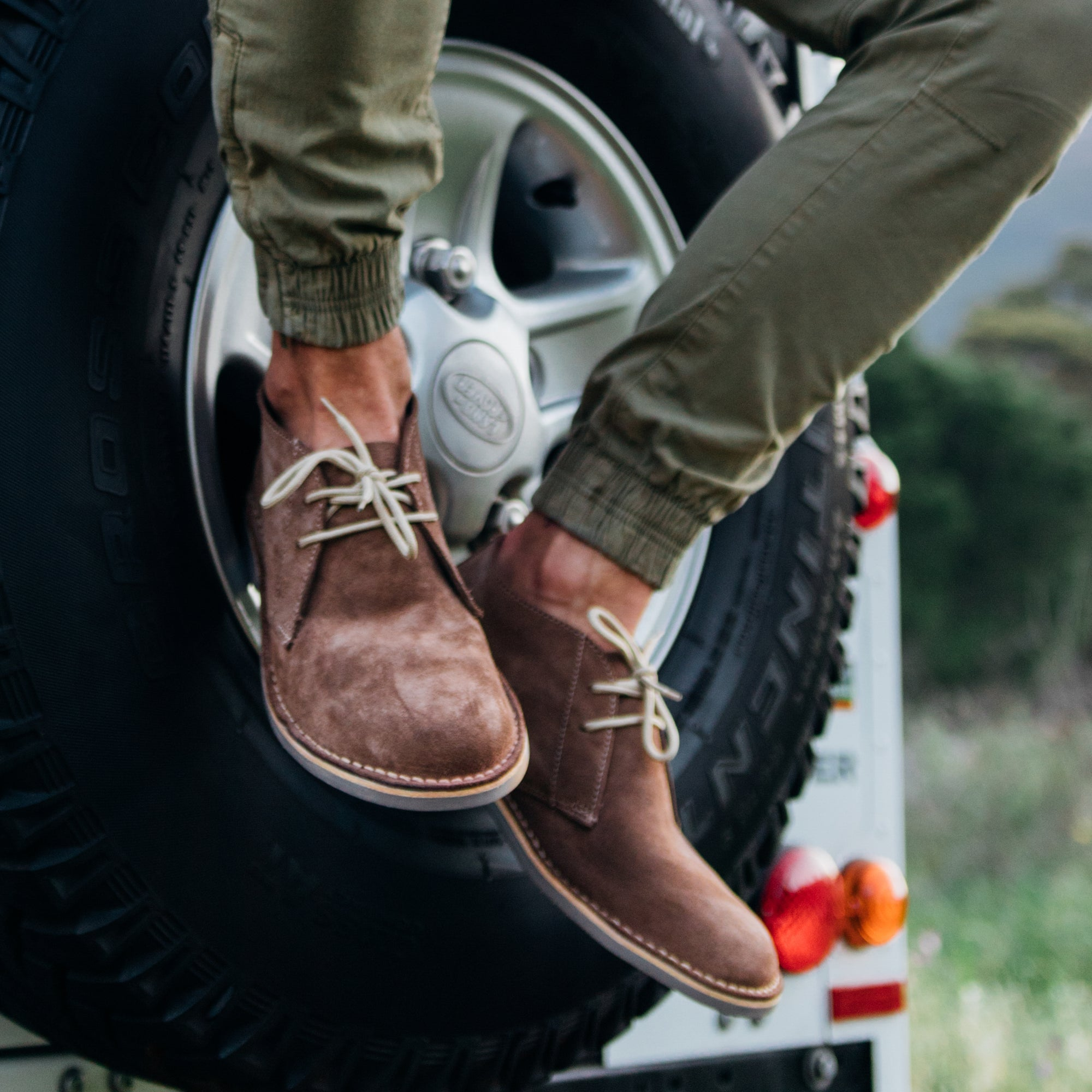 Veldskoen shoes and boots or known as vellies chukka boot ethically and sustainably handcrafted in South Africa sold in united states man wearing grey suede veldskoen sitting on a landrover discovery back wheell