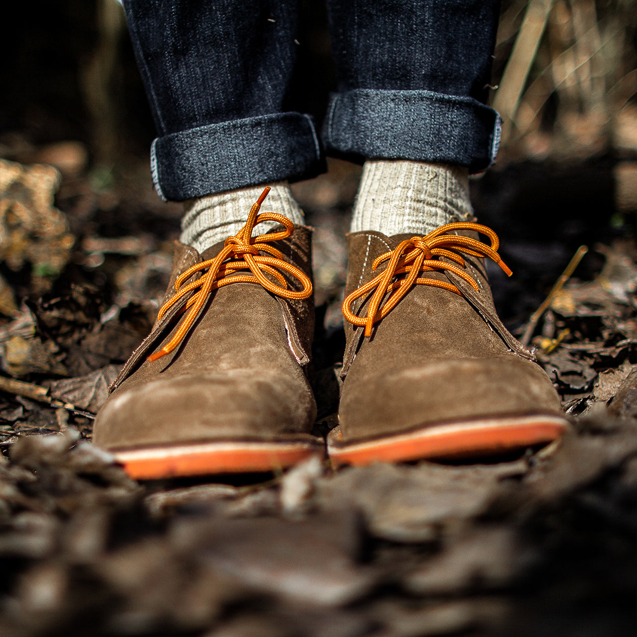 Veldskoen shoes and boots or known as vellies heritage boot ethically and sustainably handcrafted in South Africa sold in united states man wearing rolled up jeans with beige socks and suede veldskoen with ornage laces and orange soles