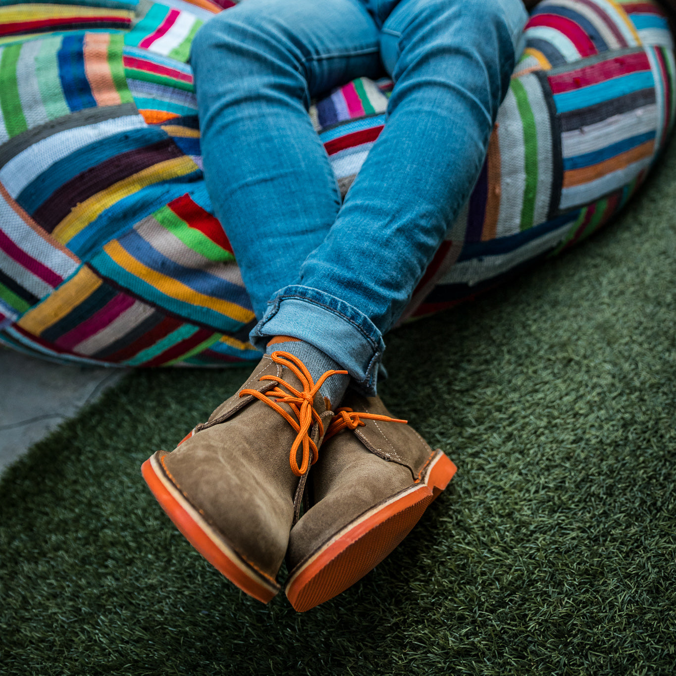 Veldskoen shoes and boots or known as vellies heritage boot ethically and sustainably handcrafted in South Africa sold in united states man sitting on a multi color beanbag wearing orange bloen heritage veldskoen and blue jeans sitting cross legged