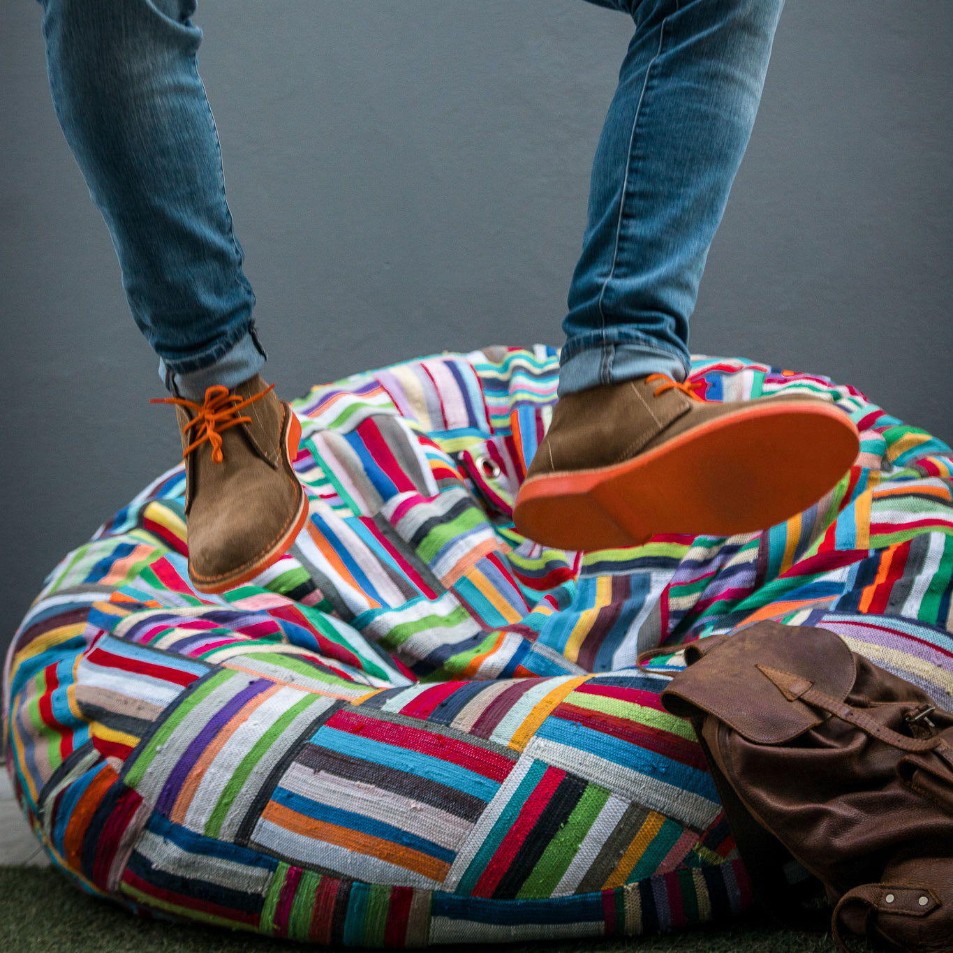 Veldskoen shoes and boots or known as vellies heritage boot ethically and sustainably handcrafted in South Africa sold in united states man wearing tight blue jeans and jumping on a multi color bean bag mid air