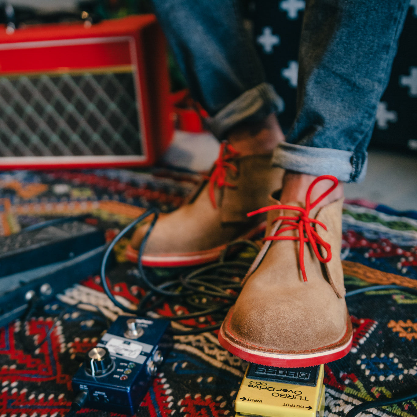 Veldskoen shoes and boots or known as vellies heritage boot ethically and sustainably handcrafted in South Africa sold in united states man weraing red laced suede heritage and playing guitar